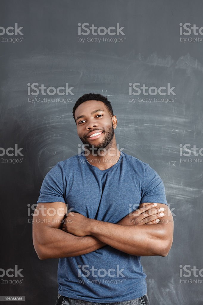 Smiling afro american man against blackboard stock photo