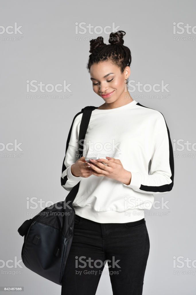 Smiling afro american teen student using smart phone Studio portrait of smiling afro american teen female student using smart phone. Studio shot, grey background. 16-17 Years Stock Photo