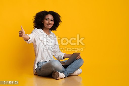 istock Smiling Afro Girl Sitting With Laptop And Showing Thumb Up Gesture 1211951153