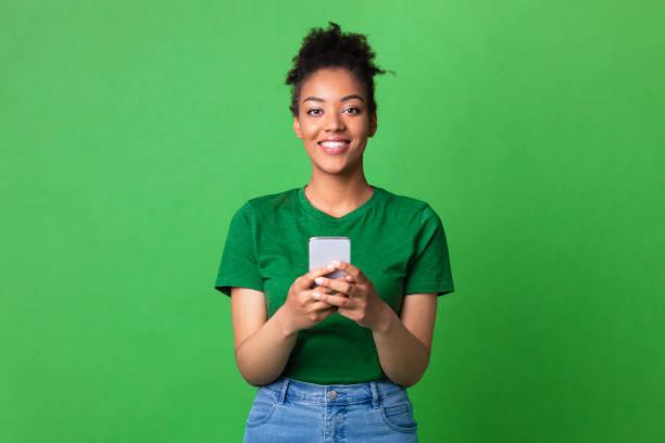 Smiling afro girl using smart phone at studio stock photo