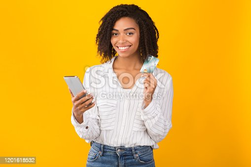 Online Store. Happy black girl holding credit card and mobile phone, ready to buy something. Copyspace, yellow studio