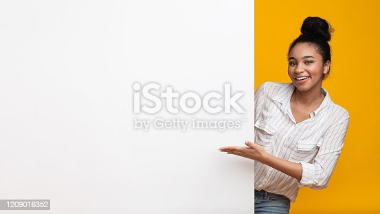 1159989540 istock photo Smiling afro woman pointing at blank advertisement board with open hand 1209016352