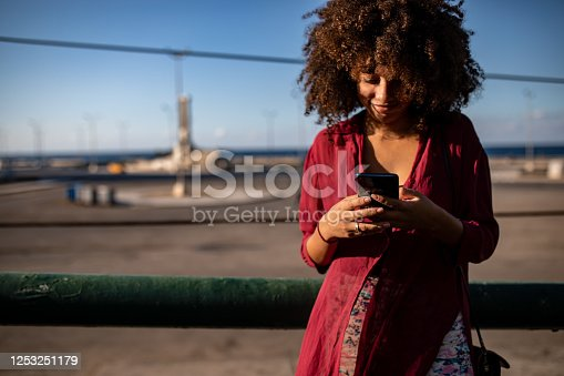 946192604 istock photo Smiling Afro woman using smartphone 1253251179