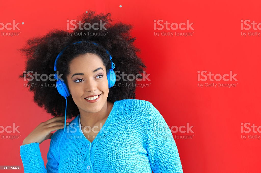Smiling afro woman with blue headphones stock photo