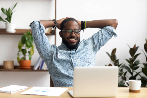 Smiling Afro-American businessman holding hands behind head sitting at office Smiling Afro-American businessman holding hands behind head sitting at office desk behind laptop. Happy black employee feeling no stress, relaxing, watching funny video after successful working relief emotion stock pictures, royalty-free photos & images
