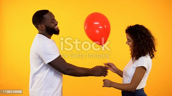 1125461272 istock photo Smiling afro-american man presenting balloon to cute woman, birthday gift, date 1158249566