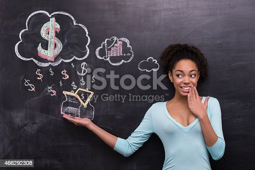 istock Smiling afro-american woman with dollar signs and purse on chalkboard 466292308