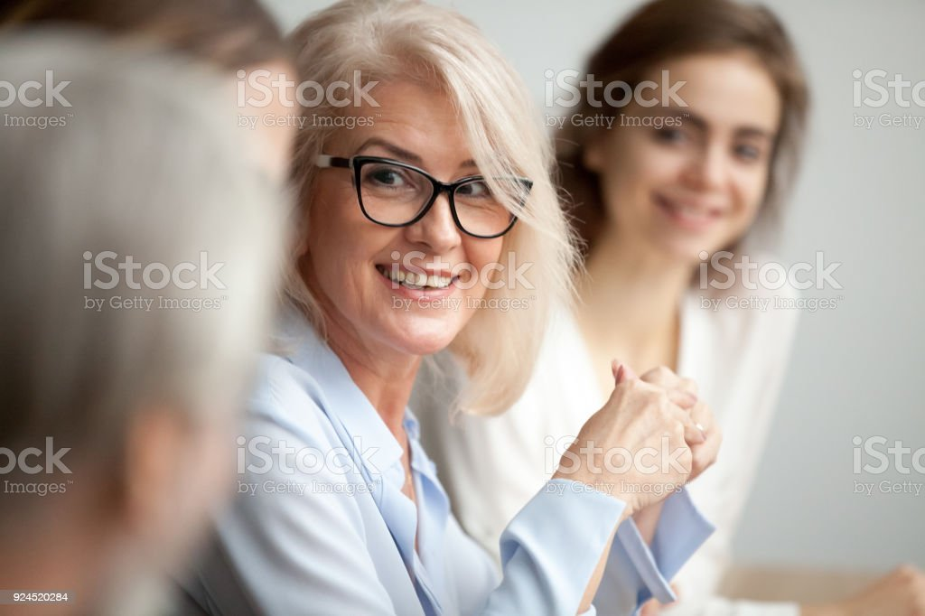 Smiling aged businesswoman looking listening to colleague at team meeting royalty-free stock photo