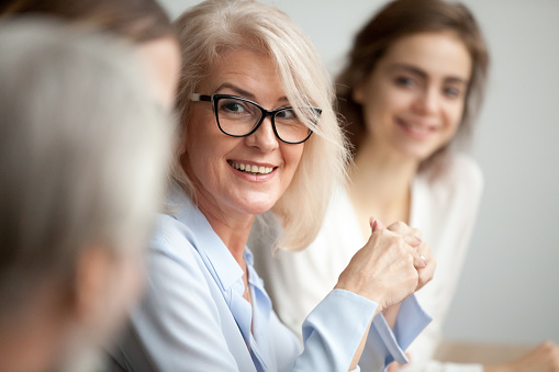 istock Smiling aged businesswoman looking listening to colleague at team meeting 924520284