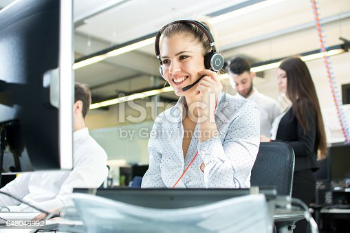 istock Smiling agent woman with headsets. Portrait of call center worker at office. 648046992