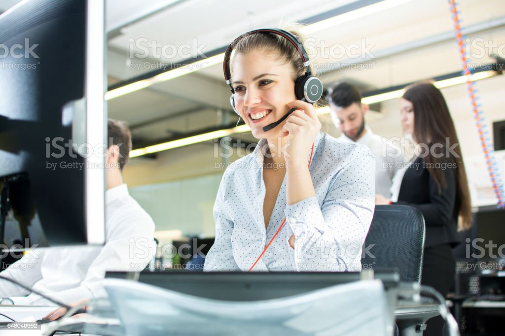 Smiling agent woman with headsets. Portrait of call center worker at office. stock photo