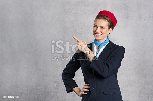 istock Smiling air hostess showing 842865288