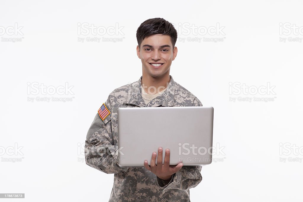 Smiling American soldier using a laptop on white background royalty-free stock photo