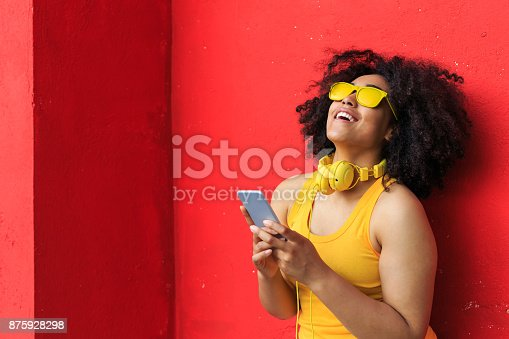 istock Smiling american-african woman listening music on smart phone 875928298