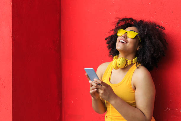 Smiling american-african woman listening music on smart phone stock photo