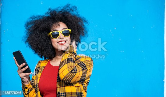 Smiling american-african woman using smart phone on a blue background