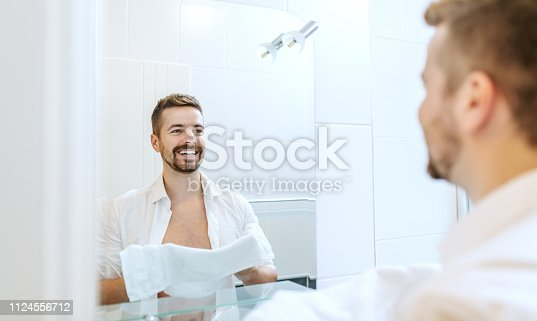 istock Smiling and cheerful businessman with unbutton shirt and towel in his hands washing his face while standing in front of mirror in bathroom. Morning routine concept. 1124556712