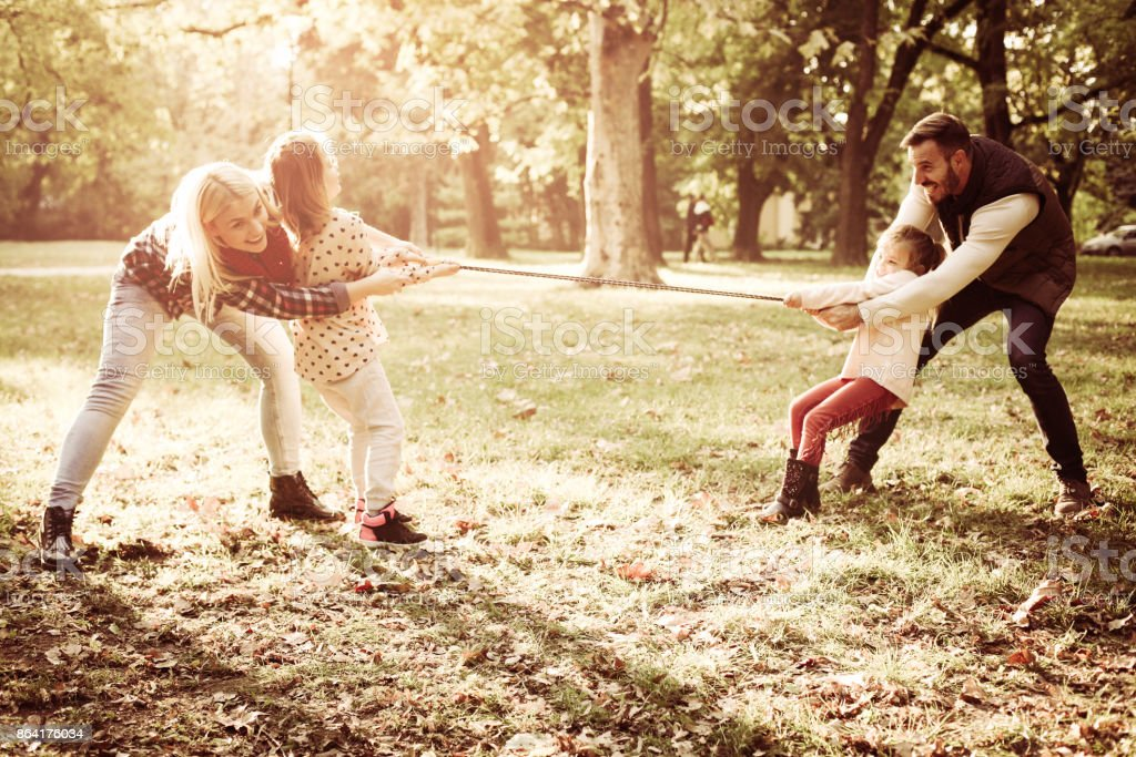 Smiling and cheerful family playing in park with rope. royalty-free stock photo