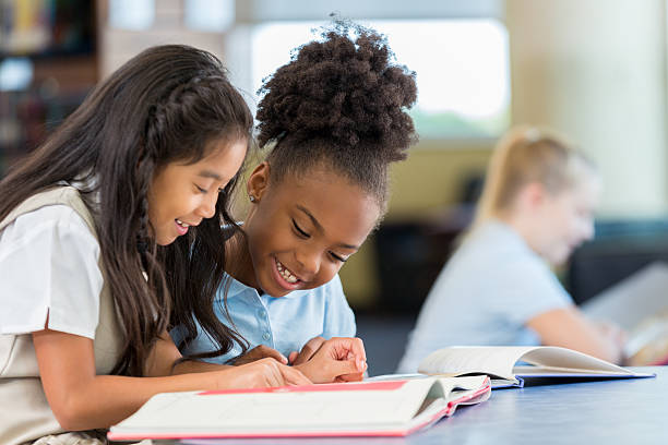 colegialas sonrientes y alegres leyendo un libro juntas en la escuela - escuela primaria fotografías e imágenes de stock