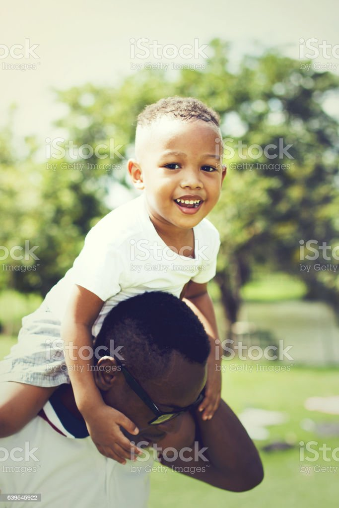 Smiling and happy African American boy carried by father stock photo