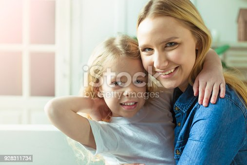 641288086 istock photo Smiling and happy mom and daughter are hugging each other at home on the couch 928311734