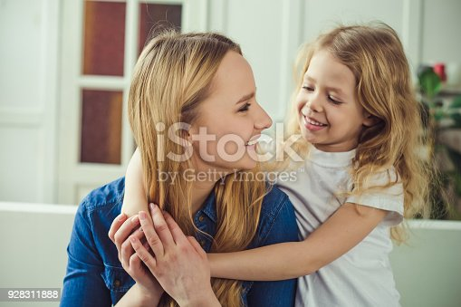 641288086 istock photo Smiling and happy mom and daughter are hugging each other at home on the couch 928311888