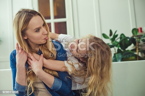 641288086 istock photo Smiling and happy mom and daughter are hugging each other at home on the couch 928311898