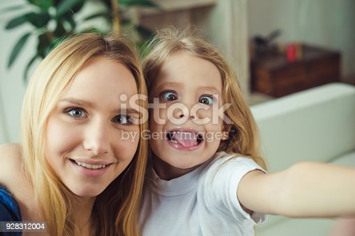 641288086 istock photo Smiling and happy mom and daughter are hugging each other at home on the couch 928312004