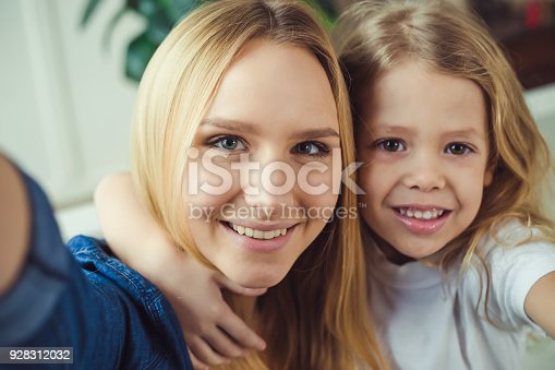 641288086 istock photo Smiling and happy mom and daughter are hugging each other at home on the couch 928312032