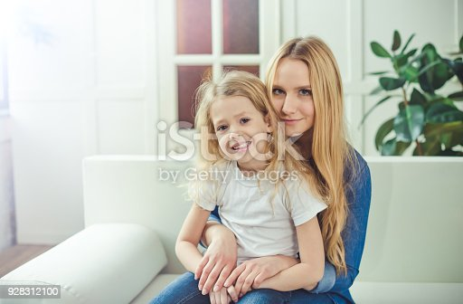 641288086 istock photo Smiling and happy mom and daughter are hugging each other at home on the couch 928312100