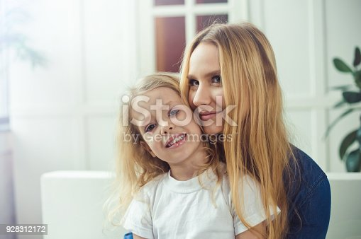 641288086 istock photo Smiling and happy mom and daughter are hugging each other at home on the couch 928312172