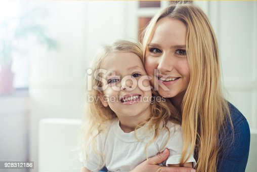 641288086 istock photo Smiling and happy mom and daughter are hugging each other at home on the couch 928312186