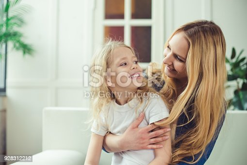 641288086 istock photo Smiling and happy mom and daughter are hugging each other at home on the couch 928312212