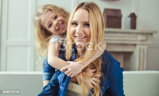 641288086 istock photo Smiling and happy mom and daughter are hugging each other at home on the couch 928312216