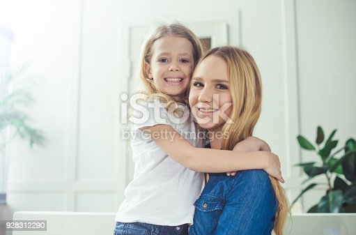 641288086 istock photo Smiling and happy mom and daughter are hugging each other at home on the couch 928312290