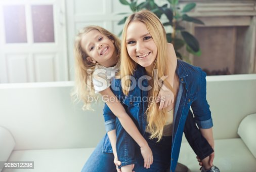641288086 istock photo Smiling and happy mom and daughter are hugging each other at home on the couch 928312298