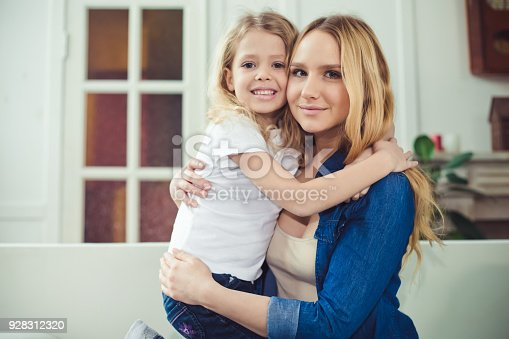 641288086 istock photo Smiling and happy mom and daughter are hugging each other at home on the couch 928312320
