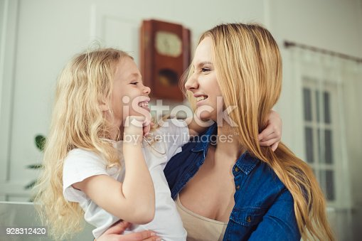 641288086 istock photo Smiling and happy mom and daughter are hugging each other at home on the couch 928312420