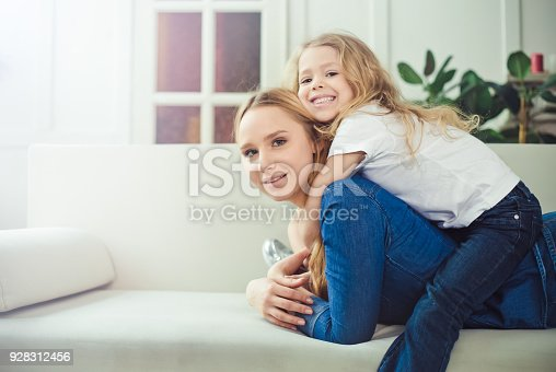 641288086 istock photo Smiling and happy mom and daughter are hugging each other at home on the couch 928312456