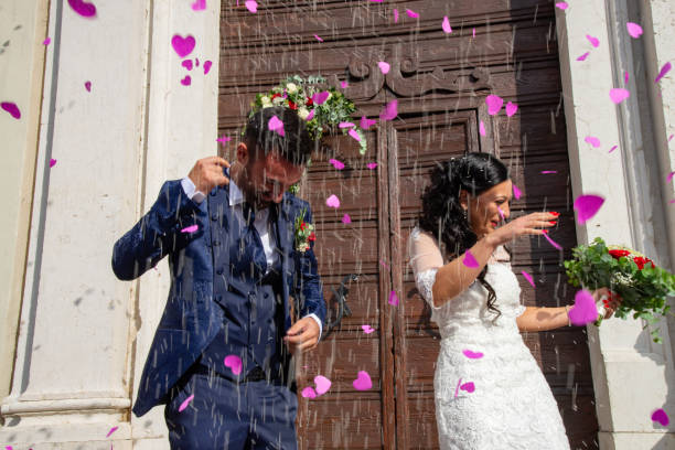 Smiling and happy young married couple leaving church after marriage. Lake Garda, Torri del Benaco, Italy. stock photo