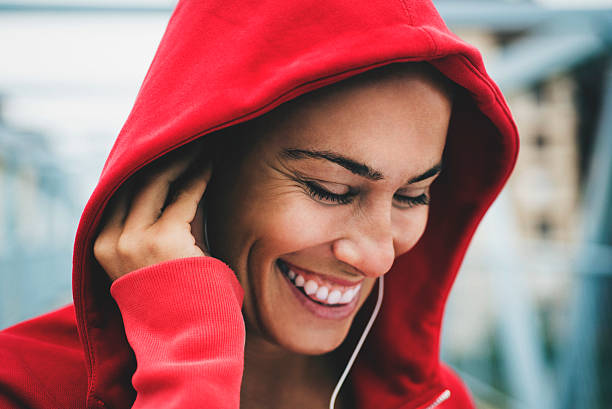 smiling and listening to music during workout - mihailomilovanovic woman listening stockfoto's en -beelden