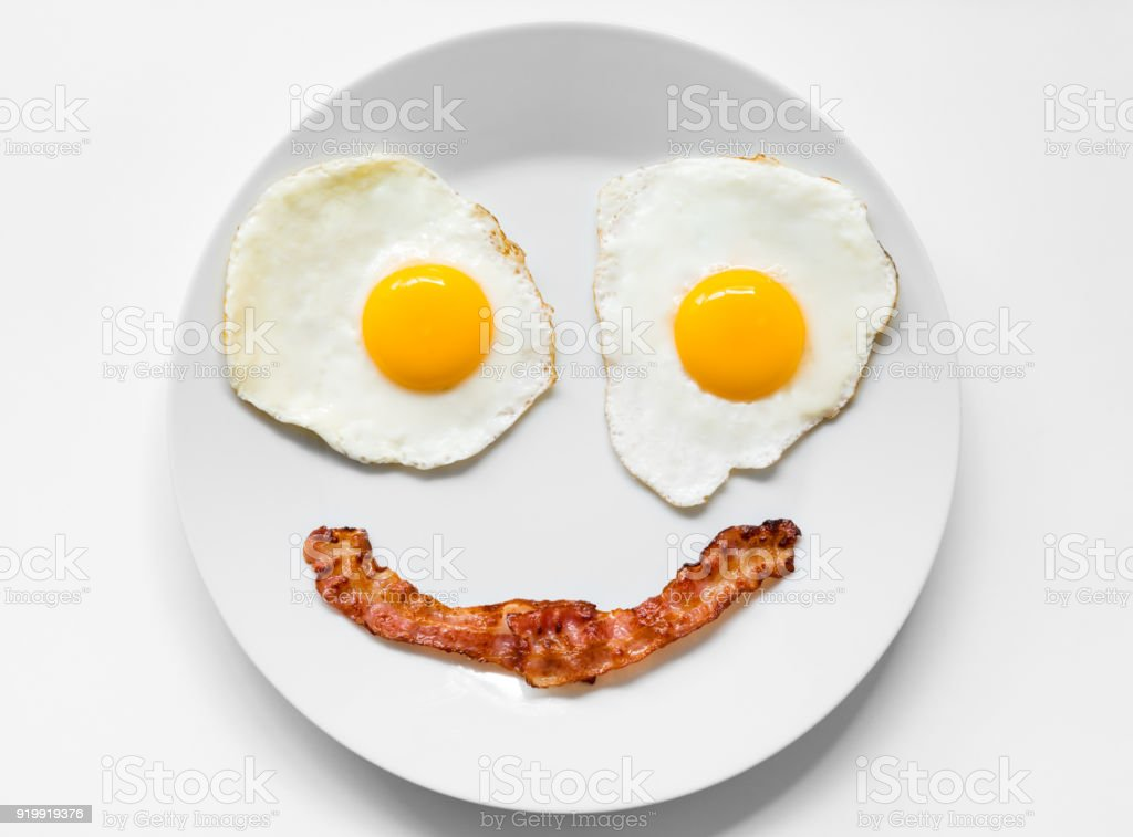 Smiling and Positive Face made from Fried Eggs and Bacon on Plate stock photo