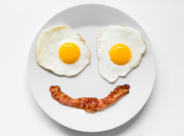 smiling and positive face made from fried eggs and bacon on plate - uovo foto e immagini stock