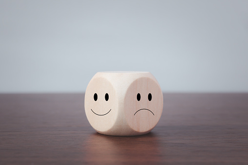 Smiling and sad symbols on wooden blocks on a gray background.
