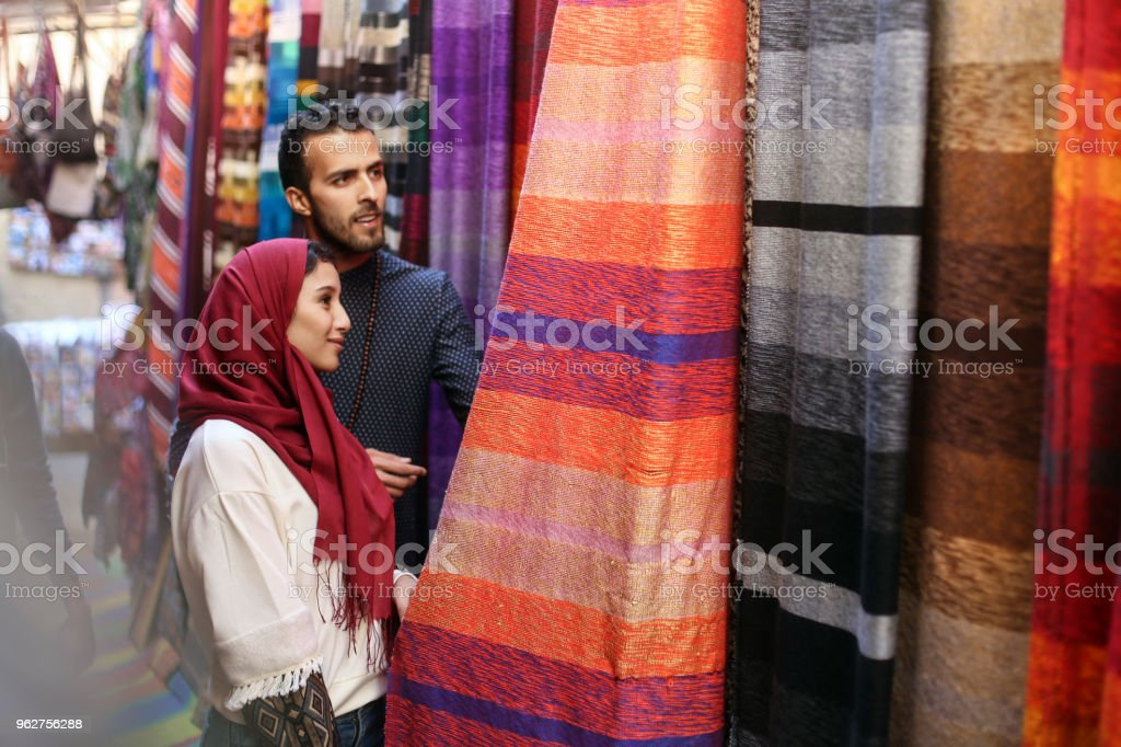 Smiling Arab couple looking at carpets stock photo