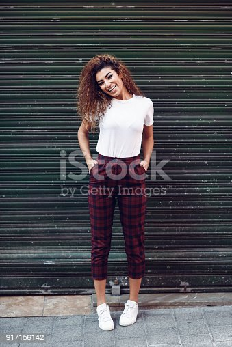 istock Smiling arab girl in casual clothes in the street. 917156142