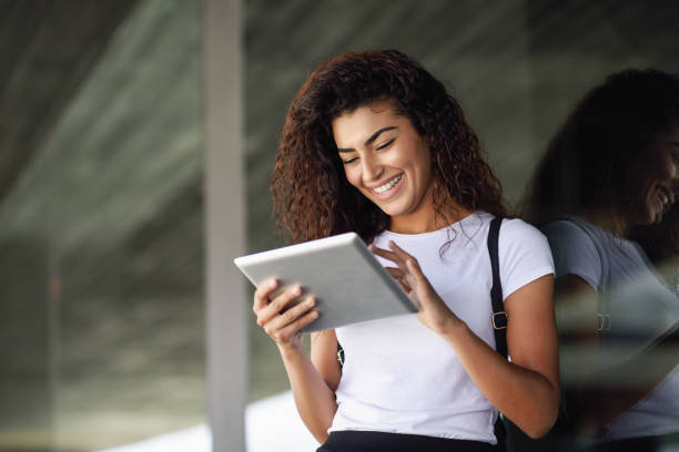 Smiling Arab girl using digital tablet in business background. stock photo