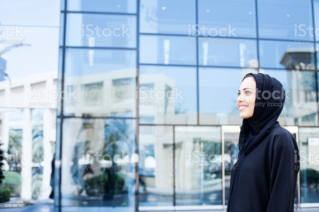 Smiling arab woman standing in front of an office building stock photo