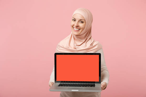 Smiling arabian muslim woman in hijab light clothes posing isolated on pink background. People religious Islam lifestyle concept. Mock up copy space. Hold laptop pc computer with blank empty screen. stock photo