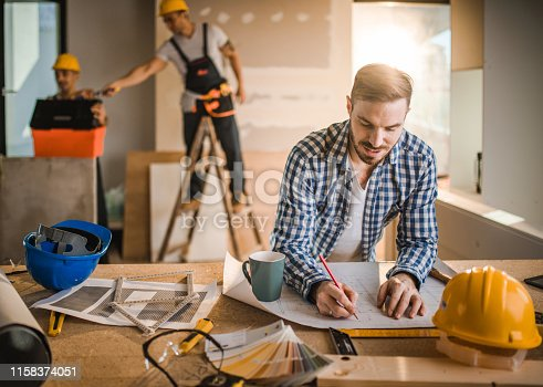 891274328 istock photo Smiling architect drawing improvements on housing plan at construction site. 1158374051